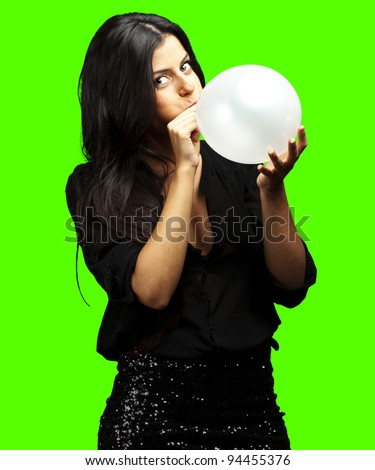 portrait of young woman blowing balloon against a removable chroma key background