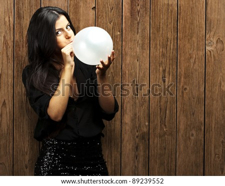 portrait of young woman blowing balloon against a wooden wall