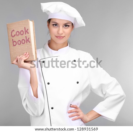Portrait of young woman chef with cookbook on grey background - stock photo