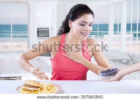 Portrait of young woman choosing to eat blueberry and refuse unhealthy cheeseburger - stock photo
