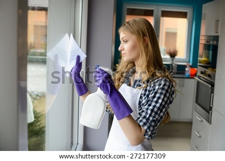 Portrait of young woman cleaning windows in the house. On her hands protective rubber gloves. Spraying detergent on glass - stock photo