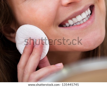 Portrait Of Young Woman Cleansing Her Face With Cotton