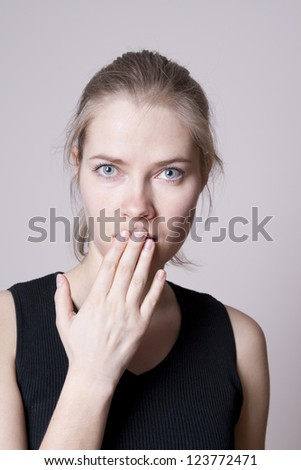 portrait of young woman covering her mouth with hand - stock photo