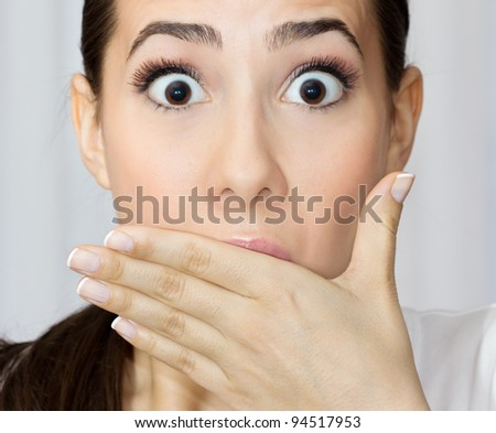 Portrait of young woman covering her mouth with hand looking shocked. - stock photo