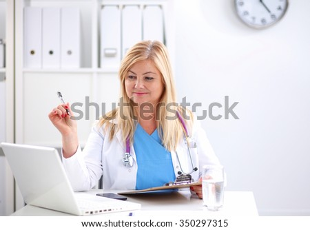 Portrait of young woman doctor in white coat at computer - stock photo