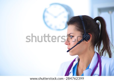 Portrait of young woman doctor in white coat at computer using phone. - stock photo