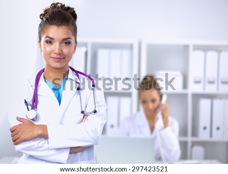 Portrait of young woman doctor with white coat standing  - stock photo