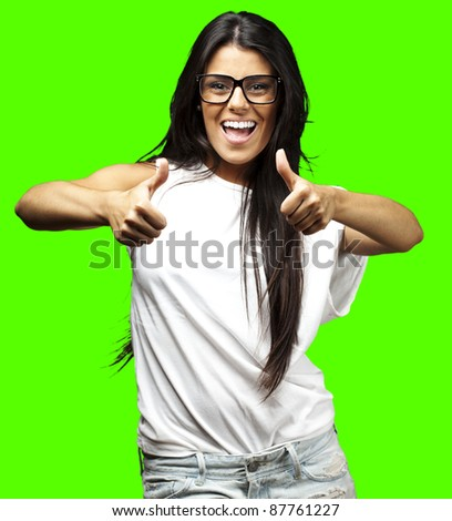 portrait of young woman doing good symbol against a removable chroma key background - stock photo