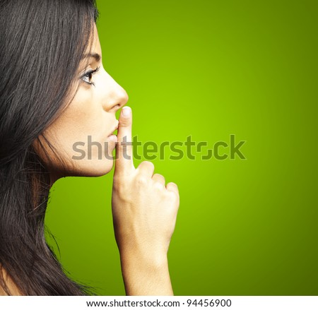 portrait of young woman doing silence sign against a green background - stock photo