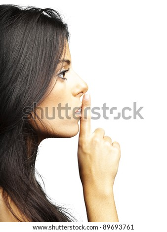 portrait of young woman doing silence sign against a white background