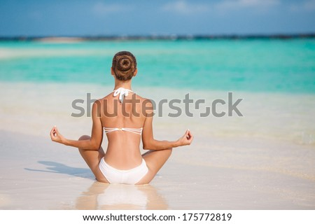 portrait of young woman doing yoga exercises on tropical maldivian beach near ocean - stock photo