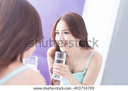 Portrait of young woman drink water and look mirror, healthcare concept,asian beauty