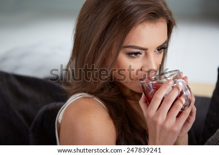 Portrait of young woman drinking tea at home sitting on sofa.