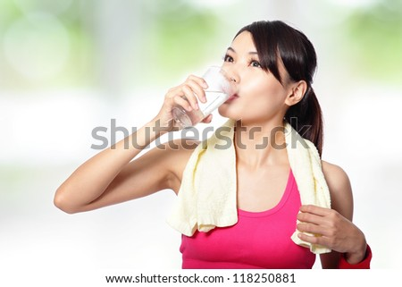 portrait of young woman drinking water after sporting with nature green background, asian beauty model - stock photo