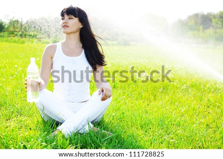 Portrait of young woman drinking water at green park - stock photo