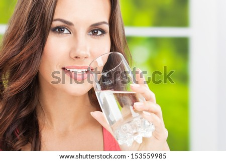 Portrait of young woman drinking water, outdoor