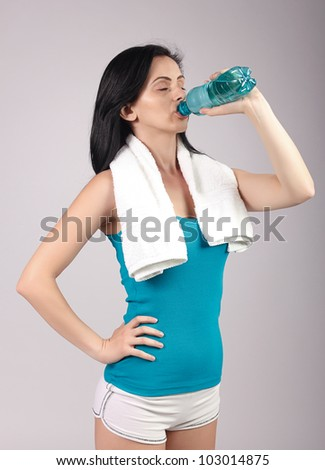 Portrait of young woman drinking water with eyes closed.Brown background. - stock photo