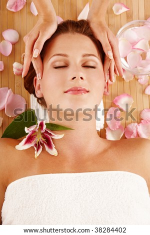 Portrait of young woman during massage in spa