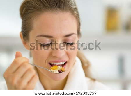 Portrait of young woman eating muesli in kitchen
