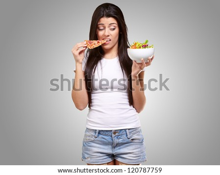 portrait of young woman eating pizza and looking salad over grey