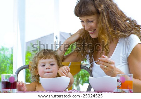 Portrait of young woman feeding her baby daughter - stock photo