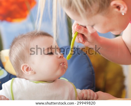 Portrait of young woman feeding her baby son - stock photo