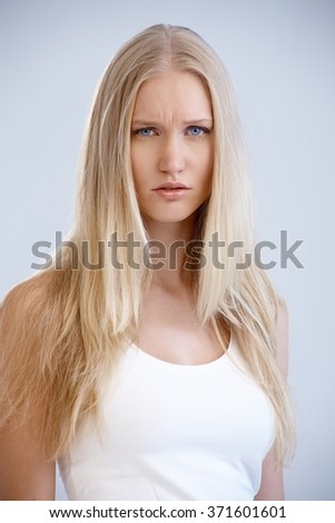 Portrait of young woman frowning, looking at camera.