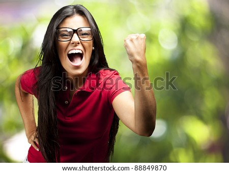 portrait of young woman gesturing victory against a nature background