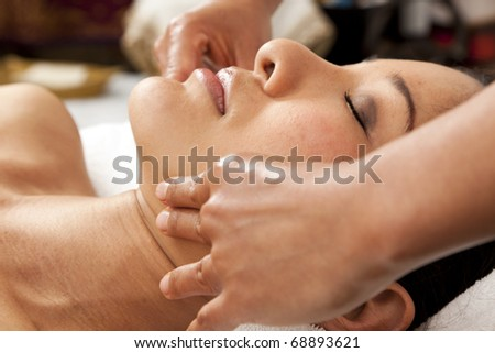 portrait of young woman having a face massage - stock photo