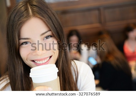 Portrait of young woman having coffee. Smiling beautiful mixed race Asian / Caucasian female is with disposable cup. She is in coffee shop. - stock photo