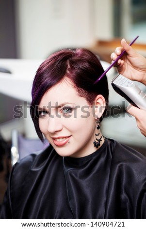 Portrait of young woman having haircut in salon - stock photo