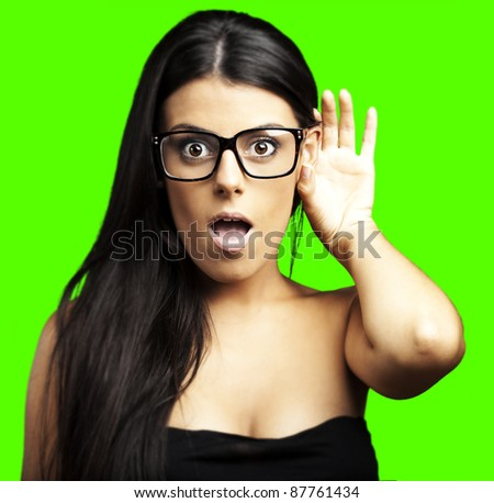 portrait of young woman hearing sound against a removable chroma key background - stock photo
