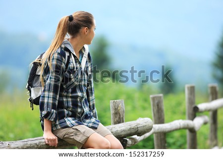 Portrait of young woman hiker sitting on a wooden fence