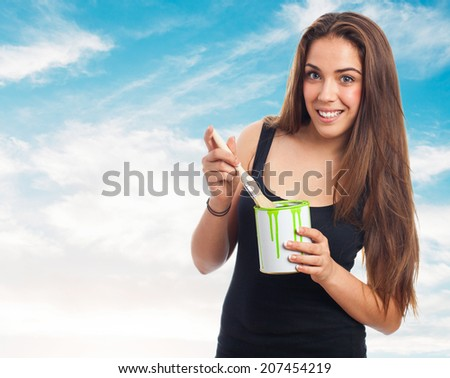 portrait of young woman holding a brush and a paint can - stock photo
