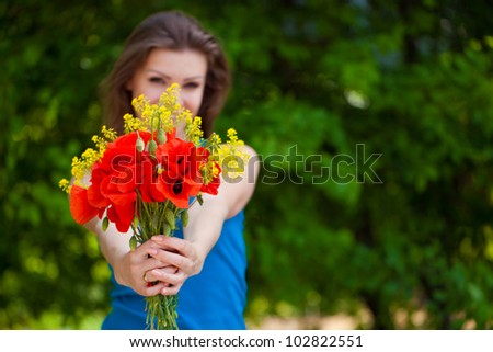 Portrait of young woman holding bunch of flowers in her hands foreground outdoor