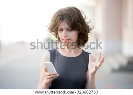 Portrait of young woman holding cellphone in hands on the street in summer, looking at screen with irritated expression, made a mistake or annoyed by texts and calls - stock photo