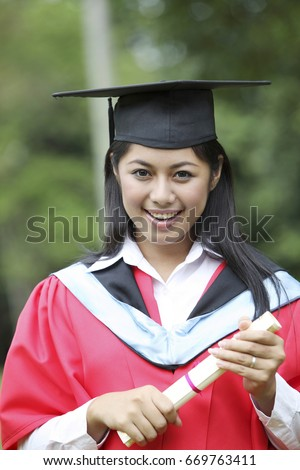 Portrait of young woman holding certificate.