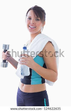 Portrait of young woman holding dumbbell and water bottle over white background