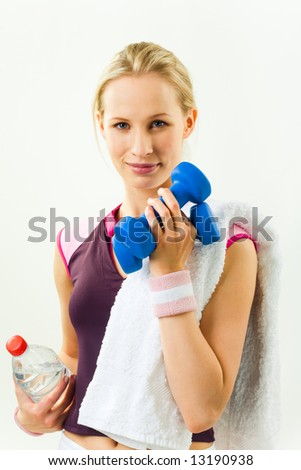 Portrait of young woman holding dumbbells and bottle of water looking at camera with smile - stock photo