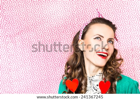 Portrait of young woman holding hearts over polka dots background - stock photo