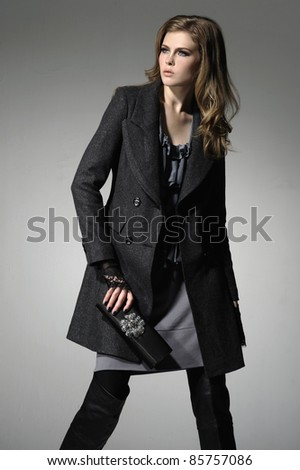 Portrait of young woman holding little purse posing on a gray background - stock photo