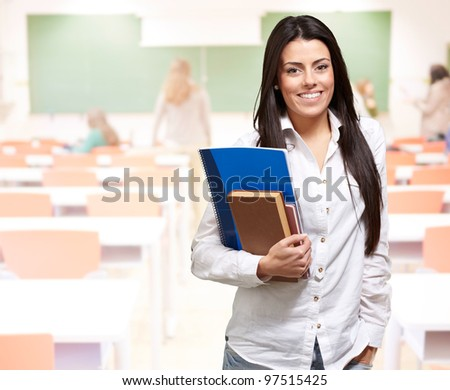 portrait of young woman holding notebook on classroom