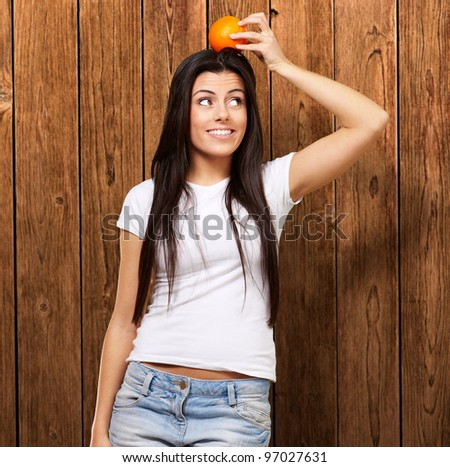 portrait of young woman holding orange on her head against a wooden wall
