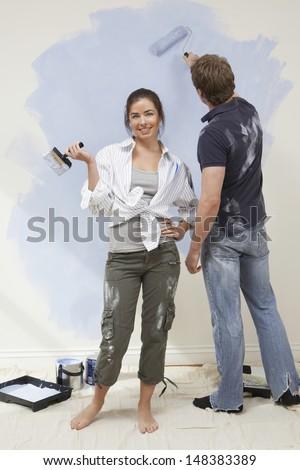 Portrait of young woman holding paintbrush while man painting wall in house - stock photo