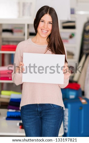 Portrait Of Young Woman Holding Placard, Indoors