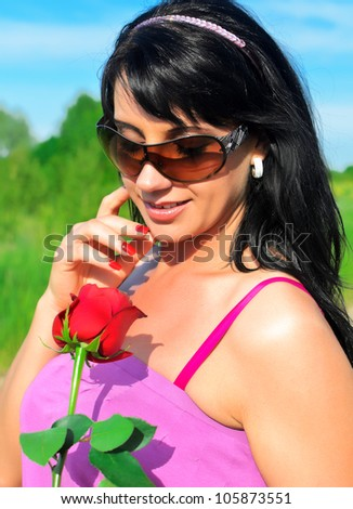 Portrait of young woman holding red rose - stock photo