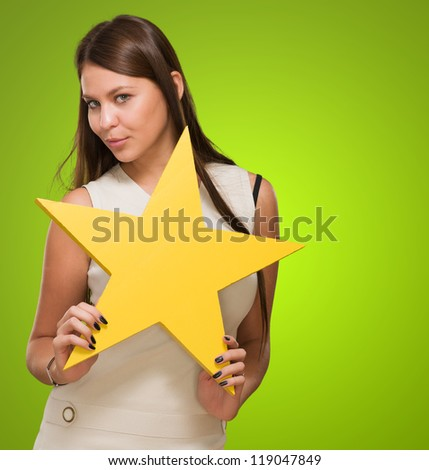 Portrait Of Young Woman Holding Yellow Star against a green background - stock photo
