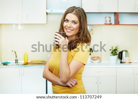 Portrait of young woman holds a cup with coffee or tea against kitchen background.