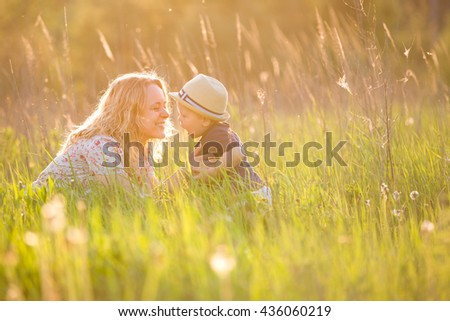 Portrait of young woman hugging her little toddler son on a sunny meadow. Happy mom with her child walking in the park on a sunny day. Mum with boy on sunset. Motherhood and lifestyle concept. - stock photo