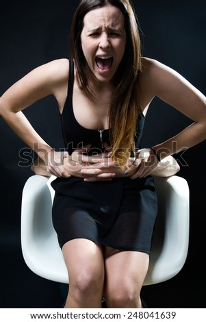 Portrait of young woman in a chair caught by a male arms. Concept of oppression. - stock photo